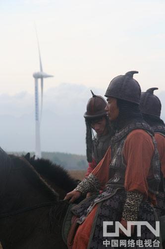 蒙古骑兵演员与康西草原上的风力发电机